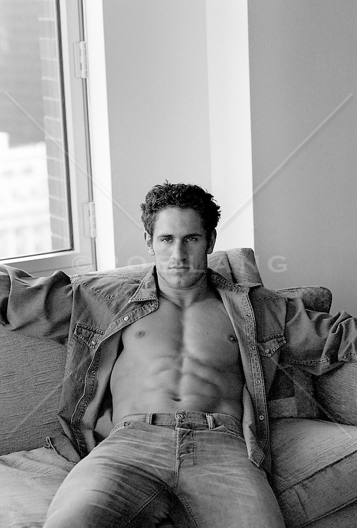sexy man with an open shirt exposing his muscular body and six pack abs while sitting at home on a couch