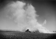 Tractor and plough raises a massive dust cloud in a desert depression below sea level converted by irrigation waters from the Colorado River into rich farmland, as long the water continues to be diverted, Imperial Valley, California, USA.   Drought and decrease Rocky Mountain snowpack have diminished the flow of the Colorado River, little of which actually reaches the sea.