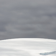 Gray skies contrast against the white gently domed top of an ice-covered hill near Melchior Island in Antarctica.