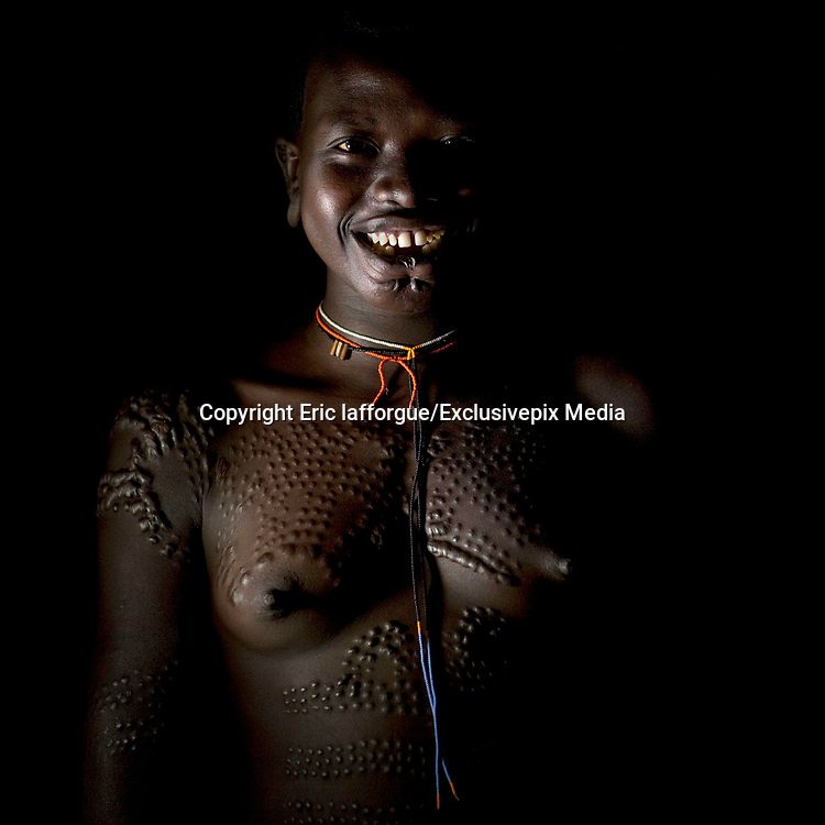 Scary Scarifications<br /> <br /> Seeing a scarification ceremony in the Surma tribe from the Omo valley in Ethiopia is a tough time. Not for the girl who is going to be scarified but for the foreigner who needs to see blood running, flies going into the wounds, under a hard sun. The girl, who was 12, did NOT say any word during the ten minutes ceremony, and did NOT show any pain. Her mother used a spine to pull the skin and a razor blade to cut the skin. <br /> At the end, i asked her if it was not too hard to have her skin cut with a razor blade, and she answered that she was close to collapse! It was incredible as she did not show any sign of pain on her face. It would be a shame for the family she confessed. A girl's eagerness to tolerate painis also an indication of her emotional maturity and willingness to bear children.<br /> The kid chooses to do it, nobody obliged her. Scarifications are a beauty sign in the tribes. This is the tradition in Surma tribe.<br /> But for years now, the kids who go to school or who convert to christian, are told not to do it anymore. The men say the lack of scars on the skins make them looking ugly.<br /> The skin of the tribes in this area has a special reaction to cutting: the cicatrisation creates raising scars. Ash and certain organic saps might be added to a wound to make the scarring more prominent and or embellished.<br /> Not far from the Surma area, the Bodi women also make scars, some even have coil scarifications on the shoulders. It is very painful as they use some metal to do this, like when they do it to their cows to mark them on the fur and the skin! Pain seems unknown in the area.<br /> I met Ana who lives in the small village of Hana Mursi. She now hides her scarifications she had at 12, as she has gone to Arba Minch town to study at the Police school. People wearing scarifications are seen as «primitives» by many urban ethiopians and they suffer from this. She is proud to introduce me to her best friend, a bod