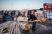 """Brother of Andrej is preparing fire wood with an axe at the barricades blockading a building supplies store named """"Epicenter"""" in the city of Lviv, Ukraine."""