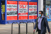 1st March, Cheltenham, England. A man walks past 'The Works' wearing a mask during the third national lockdown.