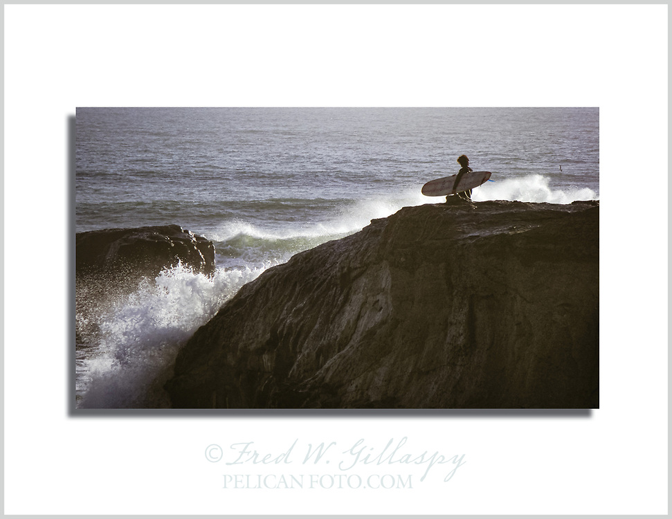 A Santa Cruz surfer on his way to the enjoy the early evening Monterey Bay waves near Steamer Lane.
