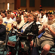 Attendees observe as President Barack Obama and First Lady Michelle Obama deliver remarks at the Disabled American Veterans  National Convention at the Orlando Hilton Ballroom in Orlando, Florida on Saturday, August 10, 2013. (AP Photo/Alex Menendez)