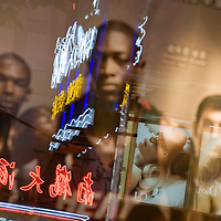 Asia, China, Shanghai, Reflection of neon signs in poster of American NBA basketball players along Nanjing Road, a shopping district lined with western and Chinese retail stores and restaurants.