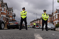 Police at the scene in Harlesden Road, London, after a woman in her twenties was shot by police and four people arrested during terror raids in London and Kent.