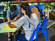 07 AUGUST 2016 - BANGKOK, THAILAND: A Thai man signs in to pick up his ballot at polling place at Wat That Thong in Bangkok. Thais voted Sunday in the referendum to approve a new charter (constitution) for Thailand. The new charter was written by a government appointed panel after the military coup that deposed the elected civilian government in May, 2014. The charter referendum is the first country wide election since the coup.      PHOTO BY JACK KURTZ