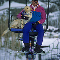 Jeff Alm and his avalanche rescue dog Chance ride a chairlift Big Sky resort in Montana.