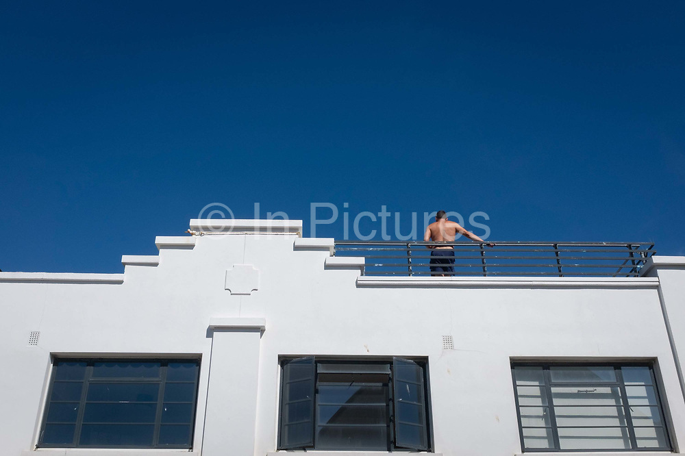 A shirtless man stands with his back to the street below on the rooftop of a bar, during cloudless blue skies of an English seaside resort, 18th July 2020, in Whitstable, Kent, England.