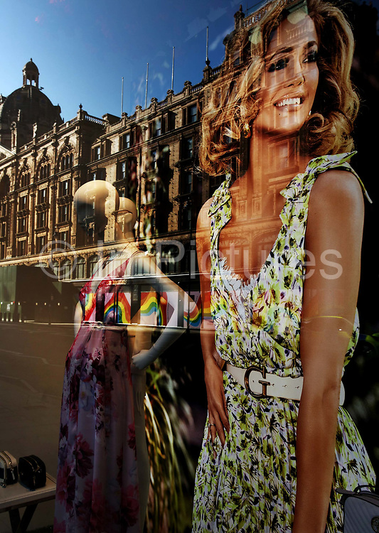 Harrods store on Knightsbridge is reflected in the window of the fashion store Guess, both locked up during the Coronavirus pandemic on 23th April 2020 in London, United Kingdom. The government clampdown includes the closure of most shops, bars and theatres throughout the country. The coronavirus forced the London luxury department store to stop trading and close its heritage store for the first time in 170 years decorating its windows with rainbows of hope.