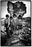 DELIZIAN, KURDISTAN, IRAQ, OCTOBER 1993. Young children collect copper and aluminium by chopping it from unexploded ordnance in an old ammunition bunker. They sell it for 10 dollarcent per kilo. Twenty million landmines and unexploded ordnance litter the former frontline in the Iran vs Iraq War still killing and maim ing Kurdish people on a daily basis.©Photo by Frits Meyst/NewsImages