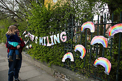 "© Licensed to London News Pictures. 01/04/2020. London, UK. A woman and a child view a 'KEEP SMILING"" hand painted sign and colourful rainbows displayed outside a school in north London. Rainbows are used as a symbol of peace and hope. <br /> <br /> ***Permission Granted***<br /> <br /> Photo credit: Dinendra Haria/LNP"