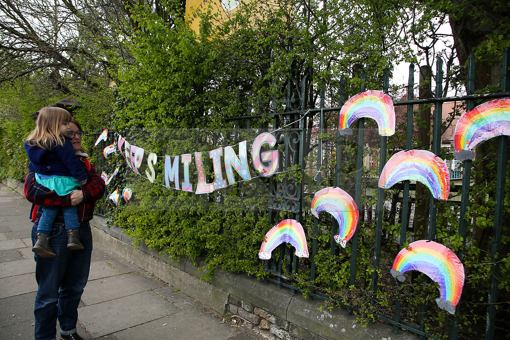 """© Licensed to London News Pictures. 01/04/2020. London, UK. A woman and a child view a 'KEEP SMILING"""" hand painted sign and colourful rainbows displayed outside a school in north London. Rainbows are used as a symbol of peace and hope. <br /> <br /> ***Permission Granted***<br /> <br /> Photo credit: Dinendra Haria/LNP"""