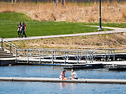 19 APRIL 2020 - DES MOINES, IOWA: Girls relax on a boat dock at Gray's Lake, a popular public park and lake south of downtown Des Moines. After a week of colder than normal weather, including three inches of snow, the weekend was spring like and people went to public parks to enjoy the pleasant weather.      PHOTO BY JACK KURTZ