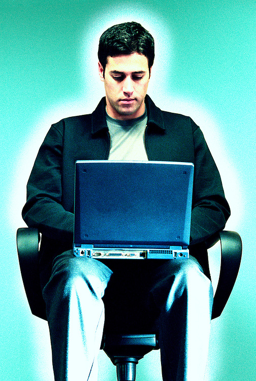 A young man sitting in an office chair working on a laptop computer on his lap.