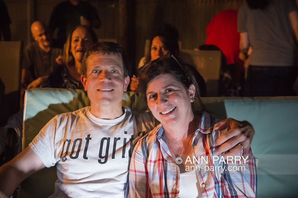 """Merrick, New York, USA. 11th June 2017.  """"American Grit"""" TV contestant CHRIS EDOM, 48, (wearing GOT GRIT? T-shirt) has his arm around shoulder of  his wife JOAN EDOM, both of Merrick, as they host backyard Viewing Party for Season 2 premiere. Show. Edom family and neighbors watched Episode 1 of FOX network reality television series that Sunday night outdoors."""