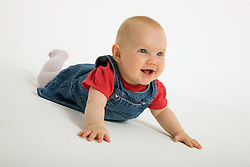 Portrait of a baby girl in the studio laughing,