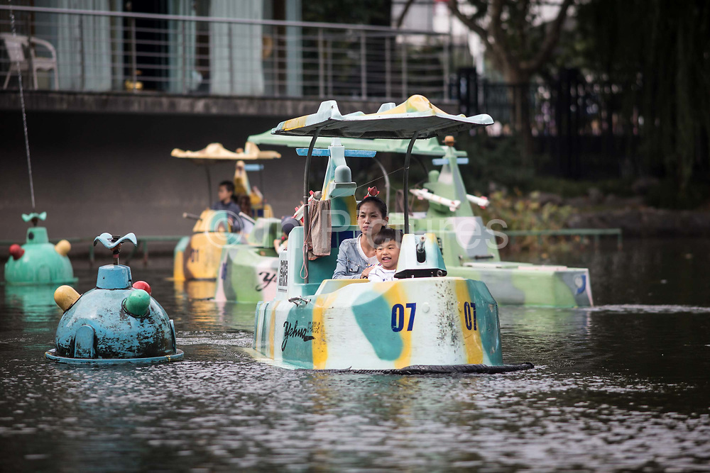A family takes a ride on a battleship-shaped pedal boat at the Lu Xun Park in Shanghai, China, on Saturday, Oct. 24, 2015.