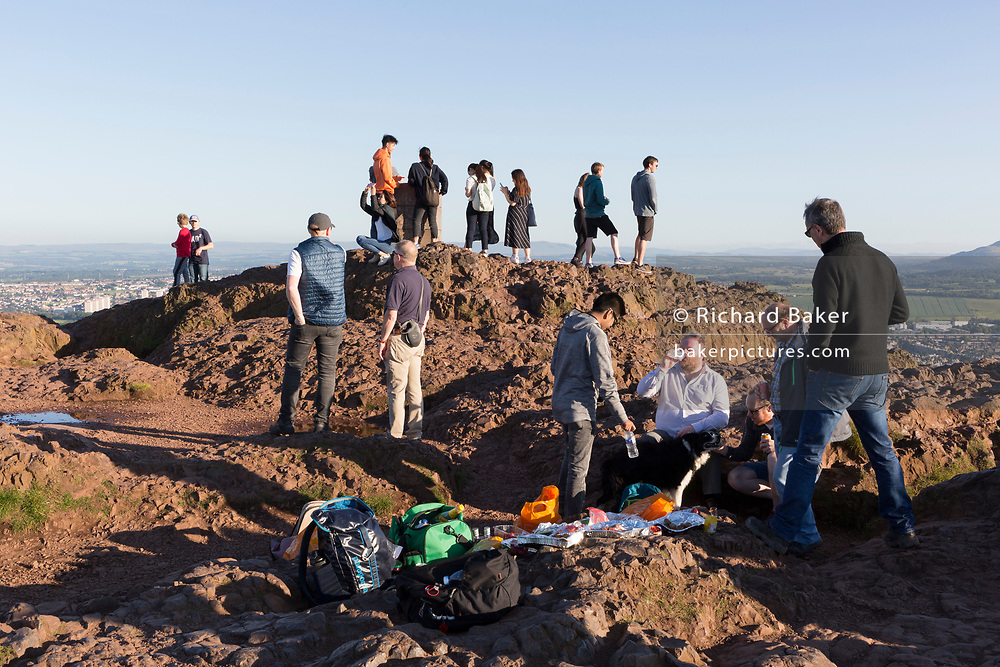 "Visitors and a group of men with drinks and food enjoy summer evening sunshine on the summit of Arthur's Seat in Holyrood Park, overlooking the city of Edinburgh, on 26th June 2019, in Edinburgh, Scotland. Arthur's Seat is an extinct volcano which is considered the main peak of the group of hills in Edinburgh, Scotland, which form most of Holyrood Park, described by Robert Louis Stevenson as ""a hill for magnitude, a mountain in virtue of its bold design"". The hill rises above the city to a height of 250.5 m (822 ft), providing excellent panoramic views of the city and beyond."