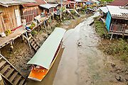 """10 JULY 2011 - AMPHAWA, SAMUT SONGKRAM, THAILAND:  A canal at low tide in Amphawa, Thailand. The Thai countryside south of Bangkok is crisscrossed with canals, some large enough to accommodate small commercial boats and small barges, some barely large enough for a small canoe. People who live near the canals use them for everything from domestic water to transportation and fishing. Some, like the canals in Amphawa and nearby Damnoensaduak (also spelled Damnoen Saduak) are also relatively famous for their """"floating markets"""" where vendors set up their canoes and boats as floating shops.      PHOTO BY JACK KURTZ"""