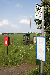 Postbox; telephone box and bus stop in rural setting,