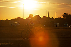 ©Licensed to London News Pictures 30/07/2020     Blackheath, UK. A cyclist heading to work. Another hot weather day is expected today in the UK as a bright warm sunrise comes up over Blackheath Common this morning in London.  Photo credit: Grant Falvey/LNP