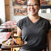 A waitress (model released) holding a plate of grilled pork ribs at Gan Shan Station, an Asian fusion restaurant opened by owner and chef Patrick O'Cain at 143 Charlotte Street in the North Asheville neighborhood of Asheville, North Carolina.
