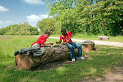 two boys playing game on log in landscape in hertfordshire