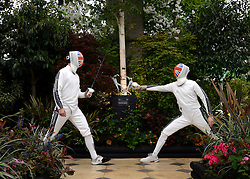 © Licensed to London News Pictures. 21/05/2012. Chelsea, UK Members of the British Fencing Team practice in a garden. Press preview of The Chelsea Flower Show today 21 May 2012. The world's most famous flower show, which has been held in the grounds of the Royal Chelsea Hospital since 1913, will be open to the public from Tuesday. Visitors are expected to flock in their thousands to see displays of plants, flowers and furniture for ideas on how to decorate their gardens.. Photo credit : Stephen Simpson/LNP