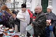 Moscow, Russia, 10/04/2004..Russian Orthodox Easter celebrations at the Church of Peter and Paul in central Moscow. Father Vasily blesses churchgoers and food they have brought..