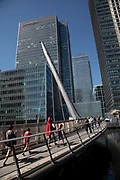Commuters walk across the South Quay footbridge over the South Dock at Canary Wharf financial district in London, England, United Kingdom. Canary Wharf is a financial area which is still growing as construction of new skyscrapers continues. Canary Wharf is London's second homoe of the British financial sector. One Canada Square skyscraper can be seen in the background.