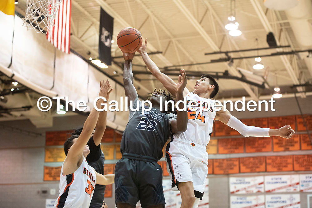 Gallup's Quinn Atazhoon (24) and Spring Valley's James Webster (23) reach for a rebound Saturday night at the Gallup Invitational boys basketball tournament at Gallup High School.