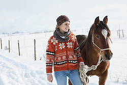 Young woman standing with horse in the farm, Bavaria, Germany