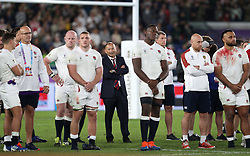 England head coach Eddie Jones (centre) stands with his players as South Africa lift the Webb Ellis Cup after the 2019 Rugby World Cup final match at Yokohama Stadium.