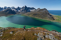 Female hiker hiking above colorful water of Flakstadpollen, Flakstadøy, Lofoten Islands, Norway