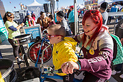 Attendee Chelsea Alford and her son Colton ride the spin art bike at the AARP Block Party at the Albuquerque International Balloon Fiesta in Albuquerque New Mexico USA on Oct. 8th, 2018.