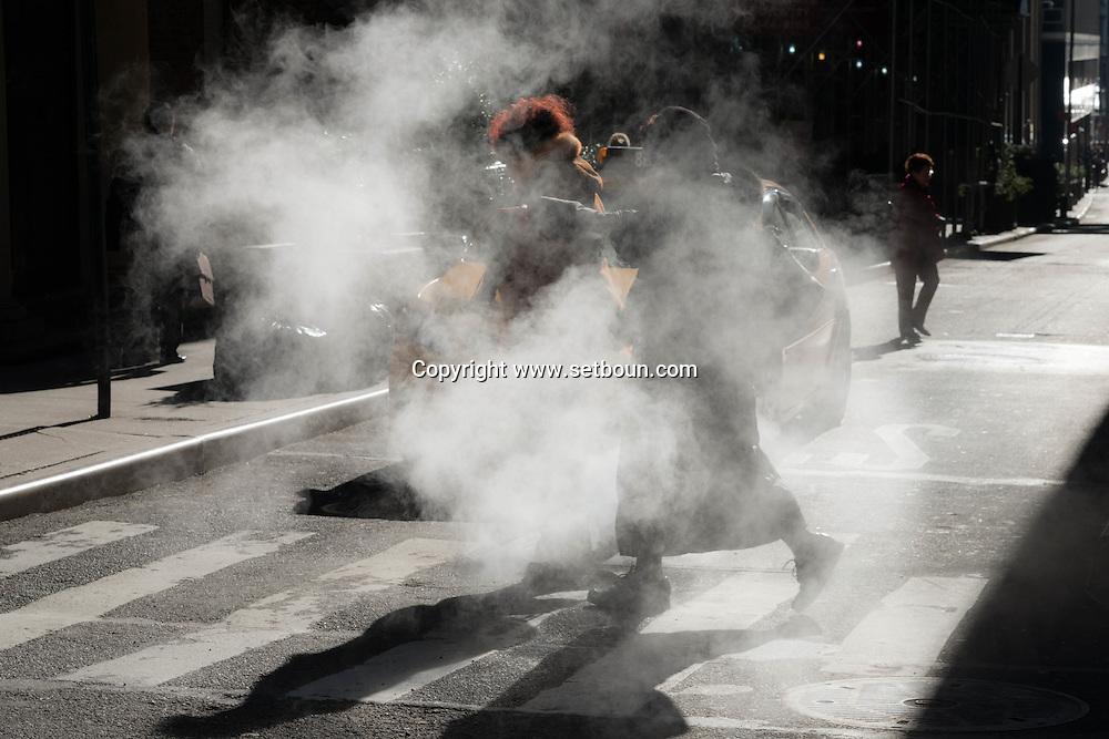 New york,  shadows of pedestrians  passing by a steam pipe,on Pine street in lower Manhattan/ Ombres des passants devant un nuage de vapeur du chauffage urbain dans Pine street