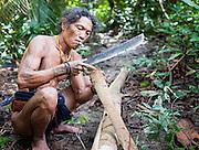 Mentawai indigenous man making a loincloth with machete (Indonesia).