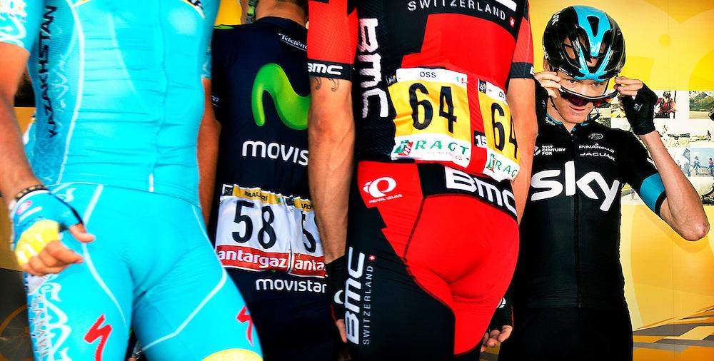 Frankrijk, Livarot, 10-07-2015.<br /> Wielrennen, Tour de France.<br /> Etappe van Livarot naar Fougeres.<br /> Chris Froome van Sky op het intekenpodium met de shirtjes om hem heen van de ploegen die ook hun favoriet hebben voor de eindzege.<br /> Foto: Klaas Jan van der Weij