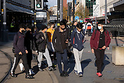 With local coronavirus lockdown measures in place and Birmingham currently set at 'Tier 2' or 'high', a goup of young men, many of whom are wearing face masks walk along the busy end of Corporation Street in the city centre on 26th October 2020 in Birmingham, United Kingdom. The three tier system in the UK has levels: 'medium', which includes the rule of six, 'high', which will cover most areas under current restrictions; and 'very high' for those areas with particularly high case numbers. Meanwhile there have been calls by politicians for a 'circuit breaker' complete lockdown to be announced to help the growing spread of the Covid-19 virus.