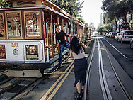 A couple has fun taking pictures on the trolley in San Francisco
