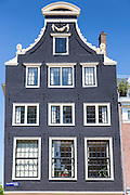 Typical canalside ornate gabled house facade - Dutch gables - in canal district in Jordaan, Amsterdam