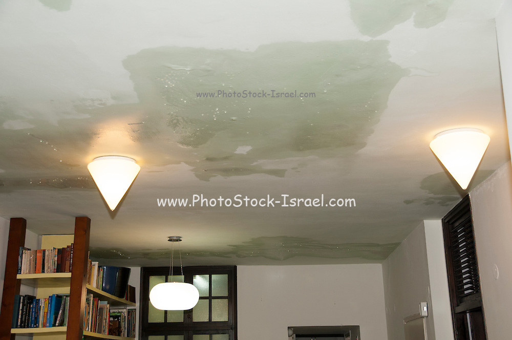Leaking ceiling water drips through a damaged roof as it rains outside