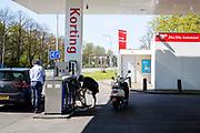 In Utrecht poetst een vrouw brandstof van haar schoen nadat ze haar brommer heeft getankt.<br /> <br /> In Utrecht a woman is cleaning her shoe afte filling up her moped.