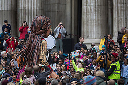 London, UK. 23rd October, 2021. Little Amal, a giant puppet of a Syrian refugee girl fleeing conflict, is welcomed by a crowd including many children at St Paul's Cathedral. The 3.5-metre puppet, which is nearing the end of an 8,000km journey from the Turkish-Syrian border to Manchester in support of refugees, climbed the steps of St Paul's Cathedral to present a wood carving of a ship at sea from St Paul's birthplace at Tarsus in Turkey to the dean.
