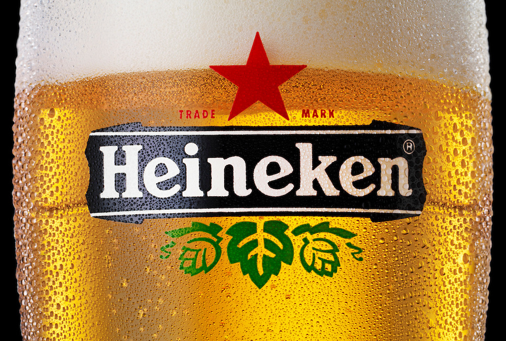 Close up of Heineken logo on Lager glass with spritz Ray Massey is an established, award winning, UK professional  photographer, shooting creative advertising and editorial images from his stunning studio in a converted church in Camden Town, London NW1. Ray Massey specialises in drinks and liquids, still life and hands, product, gymnastics, special effects (sfx) and location photography. He is particularly known for dynamic high speed action shots of pours, bubbles, splashes and explosions in beers, champagnes, sodas, cocktails and beverages of all descriptions, as well as perfumes, paint, ink, water – even ice! Ray Massey works throughout the world with advertising agencies, designers, design groups, PR companies and directly with clients. He regularly manages the entire creative process, including post-production composition, manipulation and retouching, working with his team of retouchers to produce final images ready for publication.