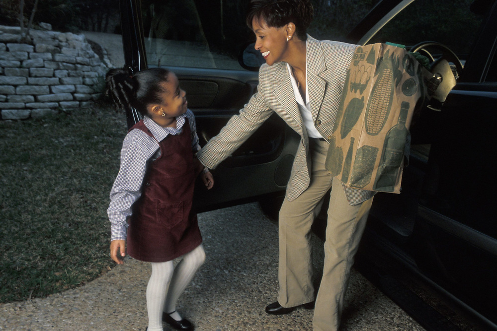 Professional African-American mother is greeted by her 5 year old daughter at the car at the end of a day in Austin, Texas.  Model Release.<br /> ©Bob Daemmrich