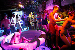 © Licensed to London News Pictures. 07/06/2014. LONDON, UK. People having fun in hot tubs as they attend 'Hot Tub Underground Cinema' at former Shoreditch Underground station in east London on Saturday, 8 June 2014. Visitors of the unique cinema enjoy a Jacuzzi with friends during classic films such as Moulin Rouge and Snatch. Photo credit : Tolga Akmen/LNP