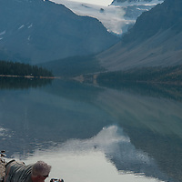 A photographer frames a scene beside Bow Lake in Banff National Park, Alberta, Canada. Behind him is the Crowfoot Glacier.