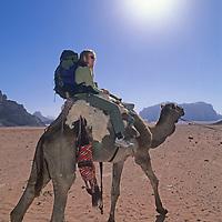 A traveler rides a camel in Jordan's Wadi Rum, part of the Arabian Desert.